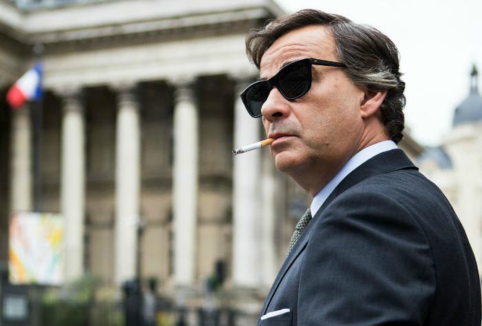Photo d'Eduard Fernandez dans le film L'homme aux mille visages d'Alberto Rodriguez où l'homme est dans Paris, semble observer quelque chose tout en fumant une cigarette. Il porte des lunettes de soleil.