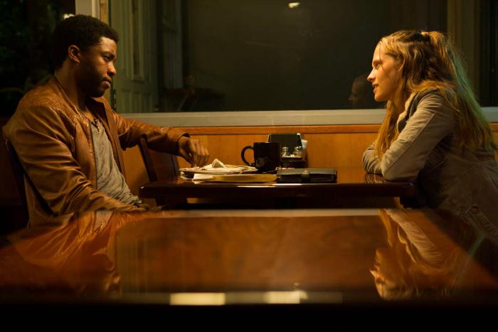 Photo de Chadwick Boseman et Teresa Palmer discutant face-à-face dans un café de Los Angeles dans le film Message from the King de Fabrice du Welz.