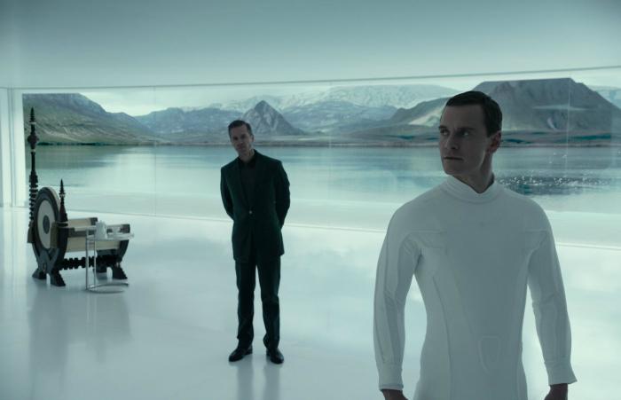 Photo de Guy Pearce et Michael Fassbender dans le film Alien : Covenant réalisé par Ridley Scott. David tourne le dos à son créateur Peter Weyland qui l'observe attentivement.