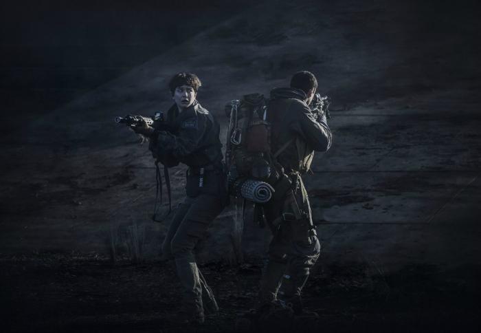 Photo de Katherine Waterston dans le film Alien : Covenant réalisé par Ridley Scott. L'héroïne tient une arme et paraît paniquée sur la planète Origae, alors qu'un autre membre de l'équipage lui tourne le dos et braque son arme dans une autre direction.