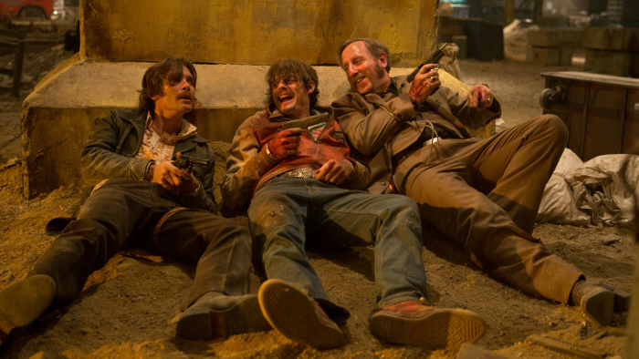 Photo de Cillian Murphy, Sam Riley et Michael Smiley étendus contre un pilier de l'entrepôt et blessés dans le film Free Fire de Ben Wheatley.