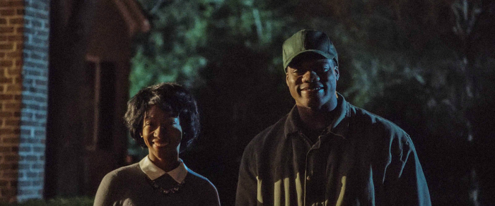 Photo de Betty Gabriel et Marcus Henderson qui sourient bizarrement face à l'objectif dans Get Out de Jordan Peele.