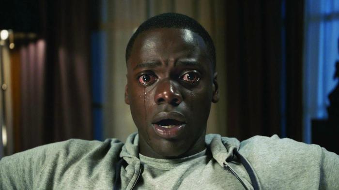 Photo de Daniel Kaluuya, assis dans un fauteuil et en larmes dans le film Get Out de Jordan Peele.