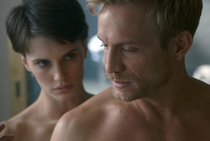 Photo tirée du film L'amant double réalisé par François Ozon sur laquelle Marine Vacth se tient derrière Jérémie Renier et l'observe de façon étrange. Ils semblent tous les deux nus.