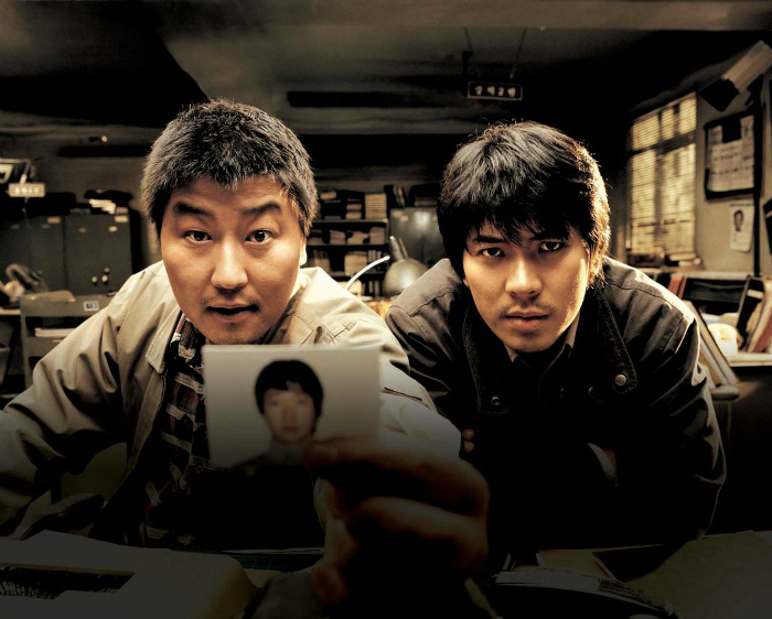 Photo des deux inspecteurs de Memories of Murder de Bong Joon-ho qui pointent la photo d'un suspect vers un témoin. Ils semblent extrêmement pressés d'entendre la réponse. La photo est prise du point de vue du témoin.