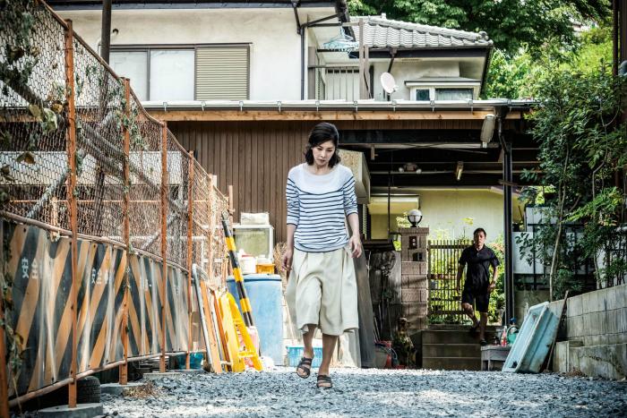 Photo de Yuko Takeushi et Teruyuki Kagawa dans le film Creepy. Ce dernier observe la première s'éloigner de sa maison.
