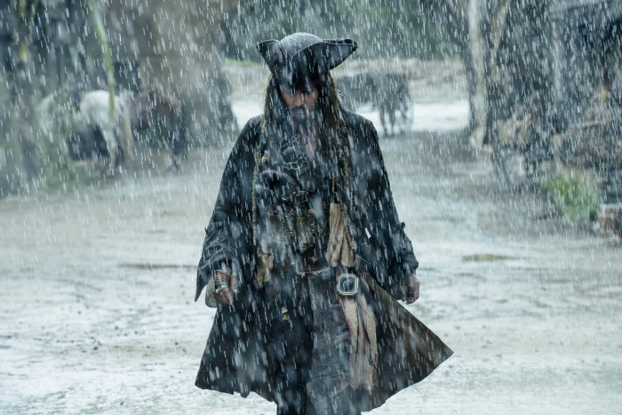 Photo de Johnny Depp dans le film Pirates des Caraïbes - La Vengeance de Salazar sur laquelle Jack Sparrow marche seul sous la pluie.