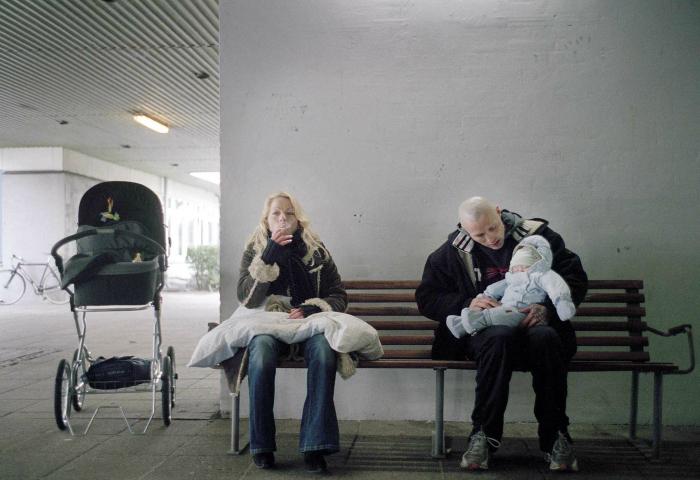 Photo tirée de Pusher II de Nicolas Winding Refn sur laquelle Charlotte et Tonny sont assis sur un banc. Tonny tient leur bébé dans ses bras.