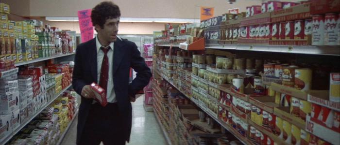 Photo tirée du film Le Privé de Robert Altman sur laquelle Philip Marlowe cherche des conserves pour son chat au supermarché en fumant une cigarette.