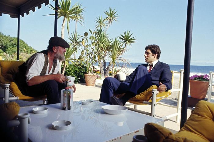 Photo tirée du film Le Privé de Robert Altman sur laquelle Sterling Hayden et Elliott Gould boivent un verre ensemble et discutent au bord de la mer.