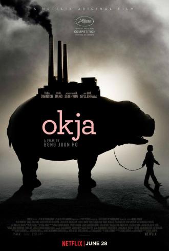 Affiche d'Okja de Bong Joon-ho sur laquelle Mija se promène avec son animal devant une lumière qui les rend à peine visibles. Sur le dos d'Okja, on peut distinguer une usine.