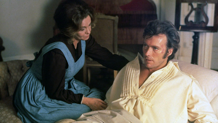 Photo de Clint Eastwood et Geraldine Page dans le film Les Proies de Don Siegel. Eastwood est blessé et allongé dans un lit et Page semble s'occuper de lui.