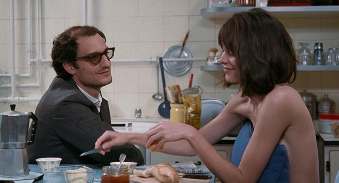 Photo de Louis Garrel et Stacy Martin dans le film Le Redoutable de Michel Hazanavicius. Les deux acteurs se sourient, assis à la table de leur cuisine où Stacy Martin prend son petit déjeuner.