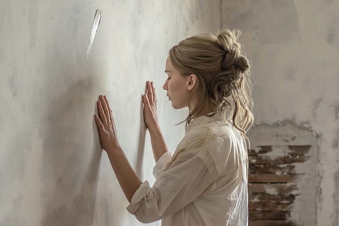 """Photo de Jennifer Lawrence dans le film """"Mother!"""" de Darren Aronofsky sur laquelle l'héroïne semble se recueillir face à un mur de sa demeure."""