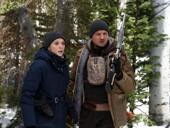 Photo d'Elizabeth Olsen et Jeremy Renner dans le film Wind River de Taylor Sheridan. Les deux acteurs sont dans une forêt enneigée. Jeremy Renner est armé d'un fusil.