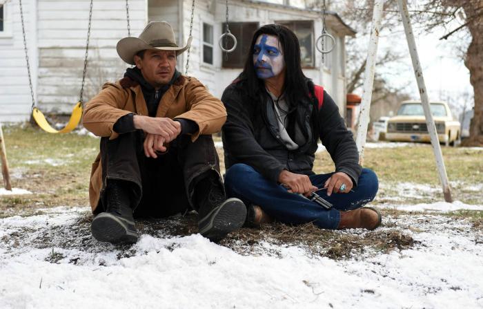 Photo de Jeremy Renner et Tokala Clifford assis dans un jardin en train de discuter dans le film Wind River de Taylor Sheridan. Tokala Clifford a le visage recouvert de peintures.