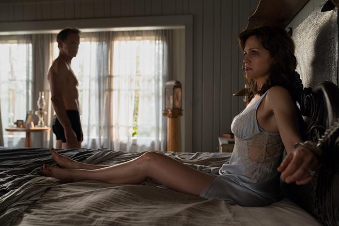 Photo tirée de Jessie de Mike Flanagan sur laquelle l'héroïne interprétée par Carla Gugino est menottée dans un lit alors que son mari interprété par Bruce Greenwood l'observe près de la fenêtre.