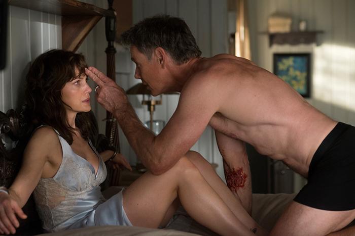 Photo tirée du film Jessie de Mike Flanagan, sur laquelle l'héroïne interprétée par Carla Gugino est menottée à son lit alors que son mari incarné par Bruce Greenwood pointe deux doigts sur son front.