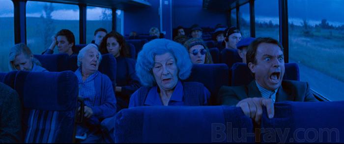 Photo tirée de L'Antre de la folie de John Carpenter sur laquelle Sam Neill hurle dans un bus. Le plan a une teinte bleue extrêmement prononcée.