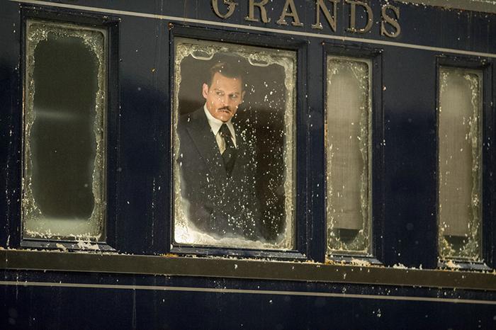 Photo tirée du Crime de L'Orient Express de Kenneth Branagh, sur laquelle Johnny Depp regarde à travers la vitre du train avec un air sombre.