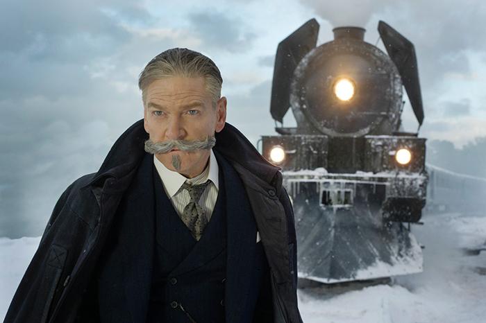Photo tirée du Crime de l'Orient Express de Kenneth Branagh, sur laquelle le comédien qui incarne Hercule Poirot se tient devant le train.