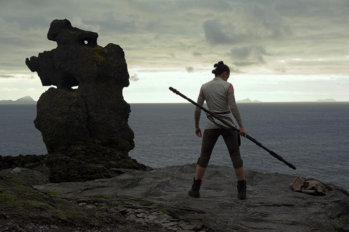Photo de Daisy Ridley dans Star Wars : Les derniers Jedi de Rian Johnson, sur laquelle on aperçoit Rey de dos sur l'île de Luke Skywalker.