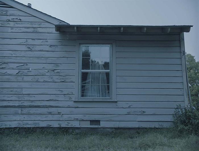 Photo de Casey Affleck vêtu d'un drap blanc et observant par la fenêtre dans A Ghost Story de David Lowery.