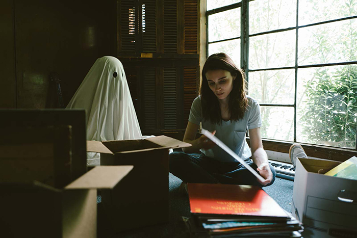 Photo de Casey Affleck vêtu d'un drap blanc et observant Rooney Mara dans le film A Ghost Story de David Lowery.