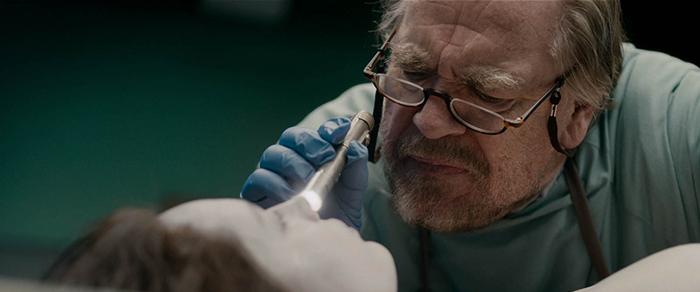 Photo de Brian Cox examinant le visage de Jane Doe dans The Jane Doe Identity.
