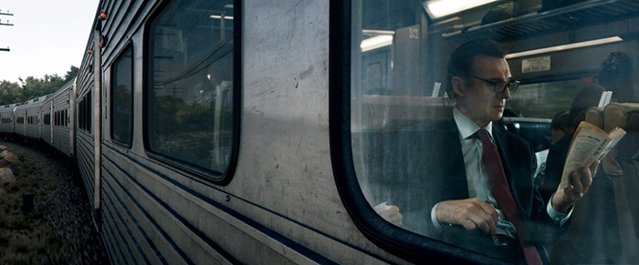 Photo de Liam Neeson lisant son journal dans le train dans The Passenger, le film de Jaume Collet-Serra.