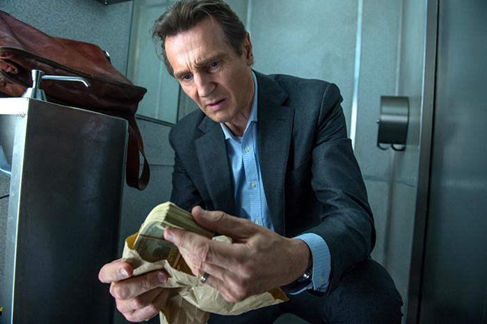 Photo de Liam Neeson tenant une liasse de billets dans le The Passenger de Jaume Collet-Serra.