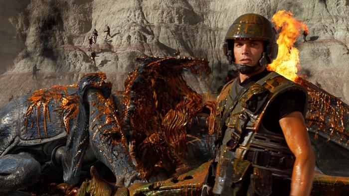 Photo de Casper Van Dien dans Starship Troopers de Paul Verhoeven, sur laquelle le soldat qu'il interprète se tient devant un énorme insecte qu'il vient d'abattre.