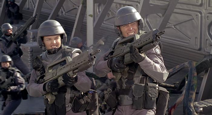 Photo de Dina Meyer dans Starship Troopers de Paul Verhoeven. Au côté d'un autre soldat, l'héroïne mitraille avec rage.