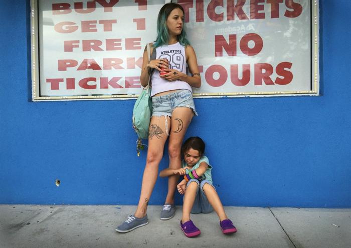 Photo tirée de The Florida Project de Sean Baker sur laquelle apparaissent Bria Vinaite et Brooklynn Prince. On y voit la petite Moonee assise, s'accrocher à la jambe de sa mère.