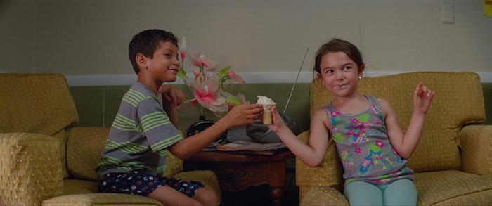Photo tirée de The Florida Project de Sean Baker, sur laquelle Scooty et Moonee s'échangent une glace avec un regard rieur lancé à un troisième personnage qu'on ne voit pas.