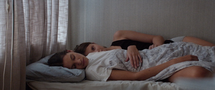 Photo tirée du film Thelma de Joachim Trier sur laquelle Eili Harboe et Kaya Wilkins sont allongées ensemble dans un lit. Eili Harboe, interprète de Thelma, fixe l'objectif.