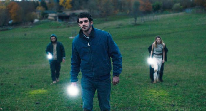 Photo tirée de Gaspard va au mariage d'Antony Cordier sur laquelle Guillaume Gouix, Félix Moati et Christa Théret marchent chacun de leur côté dans l'herbe.