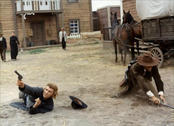 Photo tirée de Le Spécialiste de Sergio Corbucci sur laquelle Johnny Hallyday est à terre et tire sur un ennemi qui le vise depuis un toit.