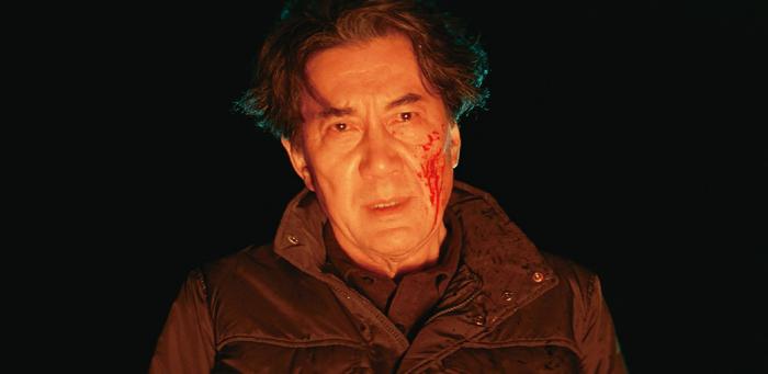 Photo tirée de The Third Murder de Hirokazu Kore-eda sur laquelle le personnage de Koji Yakusho est face à un feu, le visage ensanglanté.