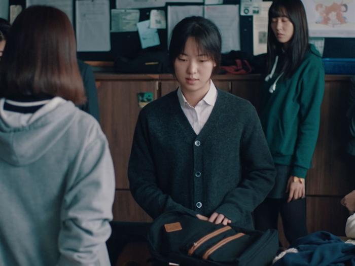 Photo tirée du film After My Death, sur laquelle le personnage interprété par Jeon Yeo-bin se tient debout dans une salle de classe, le regard vers le sol.