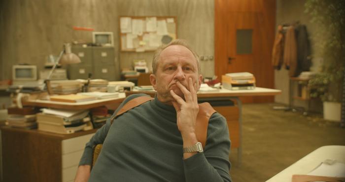 Photo tirée d'Au Poste de Quentin Dupieux sur laquelle on peut voir Benoît Poelvoorde accoudé à son bureau, sceptique.