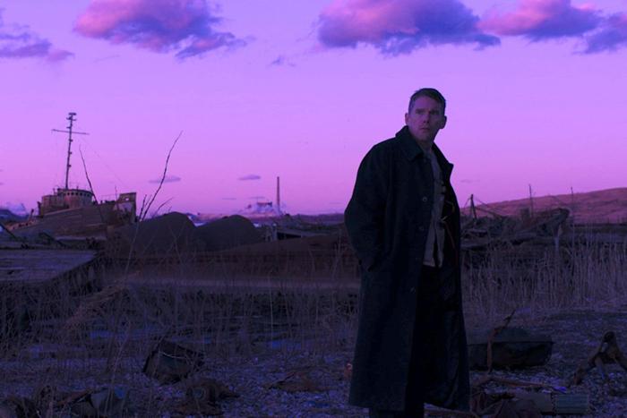 Photo tirée du film Sur le chemin de la rédemption de Paul Schrader, sur laquelle le personnage d'Ethan Hawke se tient debout, à l'aube, devant un lac extrêmement pollué.