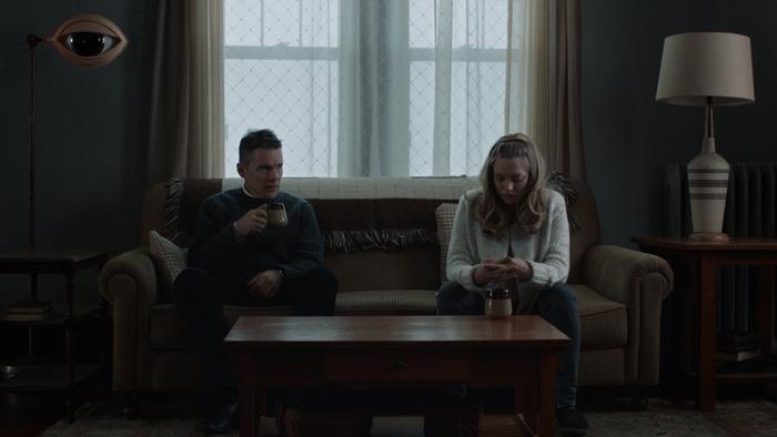 Photo tirée du film Sur le chemin de la rédemption de Paul Schrader, sur laquelle Ethan Hawke et Amanda Seyfried boivent une tasse de thé, se tenant chacun aux extrémités d'un canapé. Hawke regarde Seyfried.