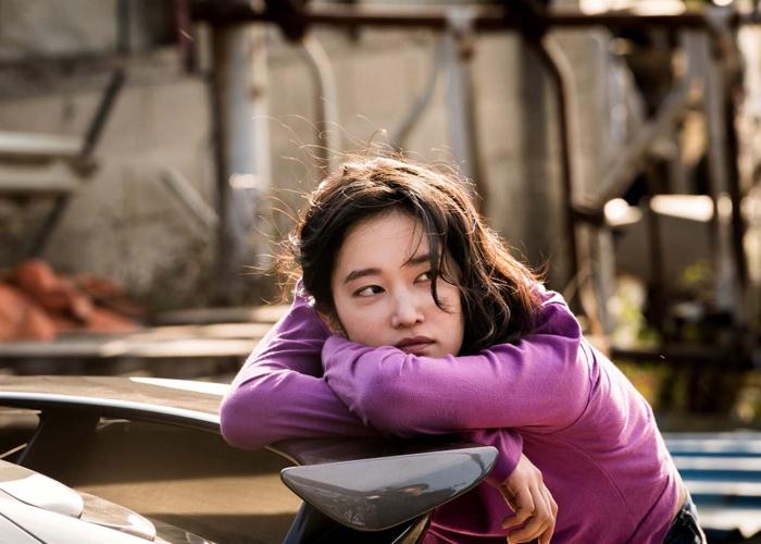 Photo tirée du film Burning de Lee Chang-Dong, sur laquelle le personnage interprétée par Jeon Jong-seo est affalé sur une trable d'extérieur et semble contempler au loin.