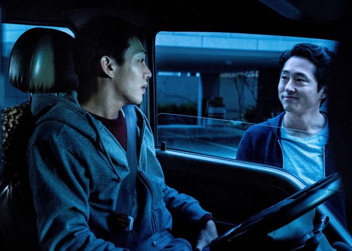 Photo tirée de Burning de Lee Chang-Dong, sur laquelle les personnages interprétés par Yoo Ah-in et Steven Yeun discutent, alors que le premier est assis à l'intérieur d'un camion et le second se tient debout à l'extérieur.
