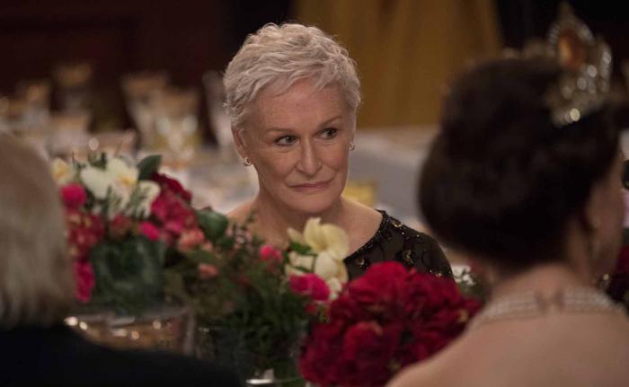"""Photo de Glenn Close tirée du film """"The Wife"""", sur laquelle elle est assise à la table d'un gala et lance un regard teinté d'amertume vers la scène."""