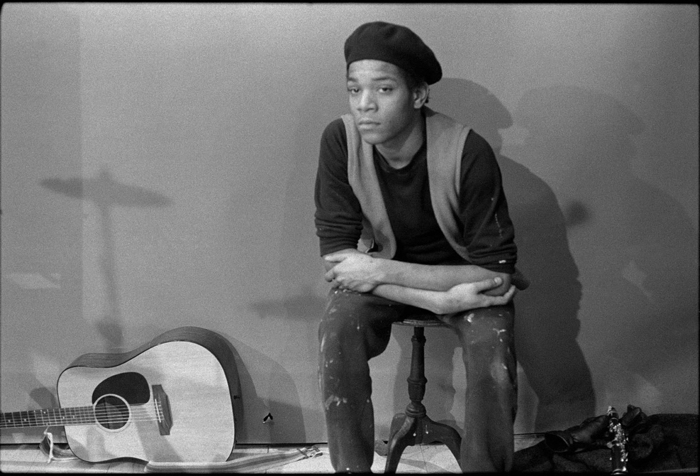 Photo en noir et blanc de Jean-Michel Basquiat, assis sur un tabouret, le regard vers l'objectif. Une guitare est posée sur le sol à sa droite.