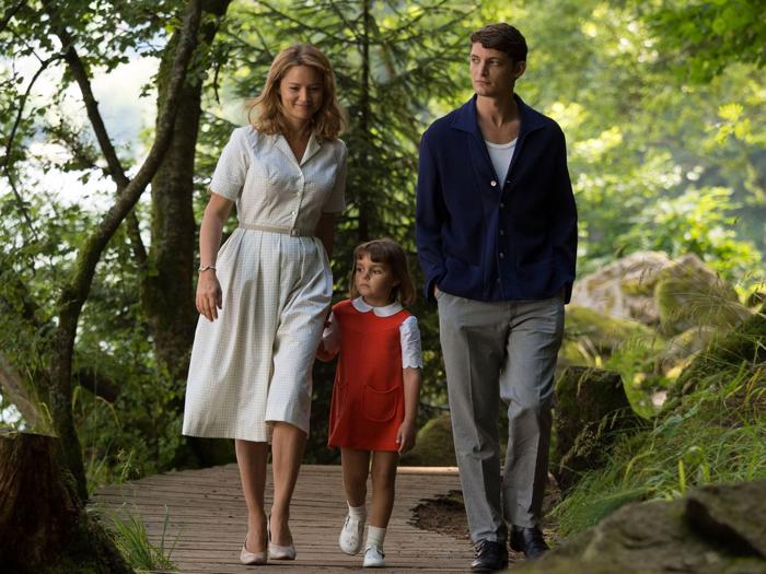 Photo tirée d'Un Amour Impossible de Catherine Corsini, sur laquelle Virginie Efira, Niels Schneider et leur fille dans le film marchent ensemble dans un bois.