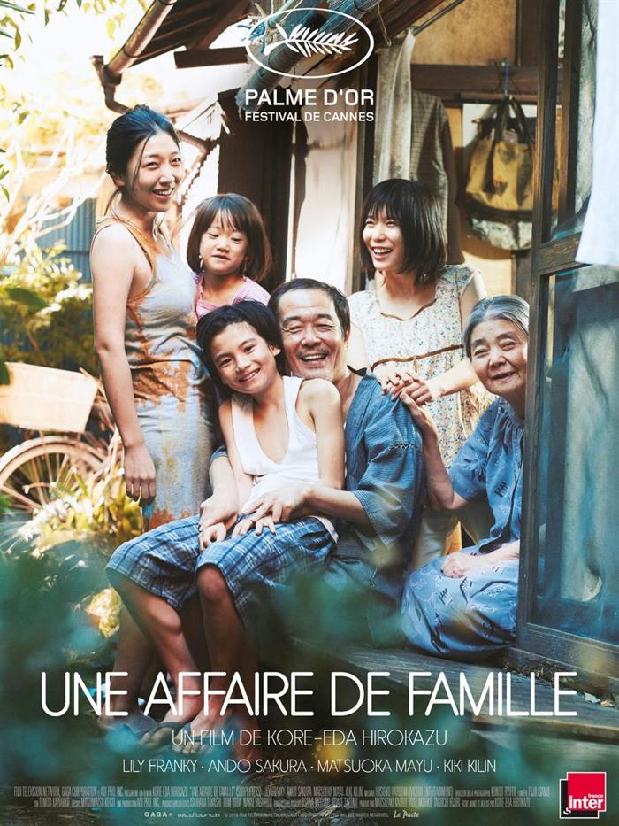 Affiche d'Une affaire de famille de Hirokazu Kore-eda sur laquelle toute la famille pose souriante face à l'objectif, dans leur petit jardin.