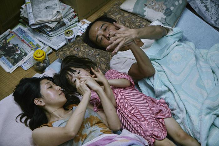 """Photo tirée d'Une affaire de famille de Hirokazu Kore-eda sur laquelle Juri, la petite fille recueillie, est entourée de sa """"mère"""" et son """"père"""". Les trois sont allongés sur le sol de leur petite maison et jouent."""